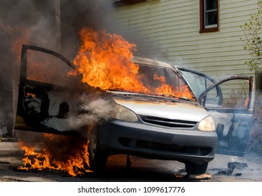 A closeup view of a burning car. Fire rages out the windows. Doors are open. Dark smoke from the flames. Badges and branding removed from car.