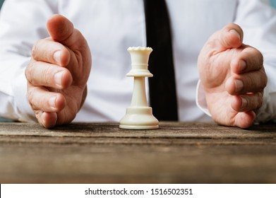 Closeup view of businessman holding protective hands around a white king chess piece.