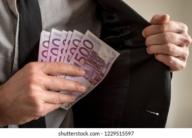 Closeup view of businessman placing six five hundred Euro bills in the inner pocket of his suit jacket. Conceptual of bribery.