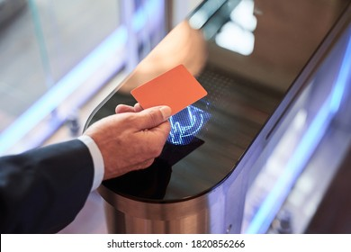 Close-up view of businessman scanning his card at turnstile gate