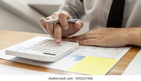 Close-up view A businessman using a calculator to calculate numbers on a company's financial documents, he is analyzing historical financial data to plan how to grow the company. Financial concept.