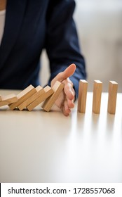 Closeup view of businesswoman interrupting collapsing dominos with her hand in conceptual image of business depression prevention.