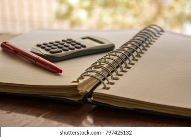 Close-up view of calculator, notepad and pencil