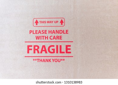 closeup view of cardboard packaging surface with red printed text This way up please handle with care fragile thank you