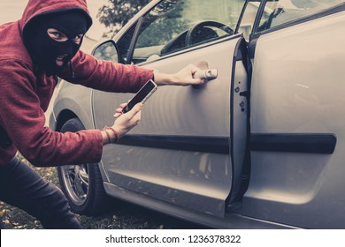Closeup view of carjacker trying to open car with pick-lock. Masked man squats and breaks someone's car looking to the viewer.