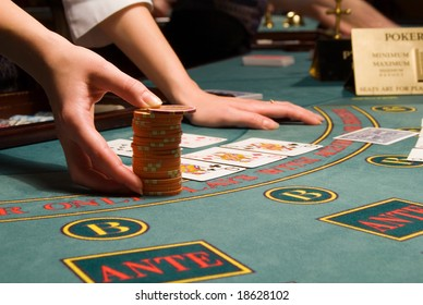 close-up view of a casino dealer handling a big pile of gambling chips at poker table