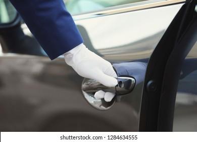 Closeup view of chauffeur opening car door