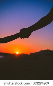 Closeup view of child and adult hands on sunset outdoors background.