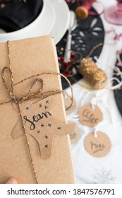 Closeup view of a Christmas gift box tied with golden ribbon . The name Sean is on the tag. More tags and an elegant dinner table is as blurred background.
