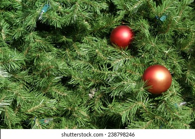 Closeup view of a Christmas tree with ornaments and lights. Ideal for use as a background.