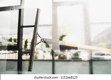 close-up view of cleaning and wiping window with squeegee