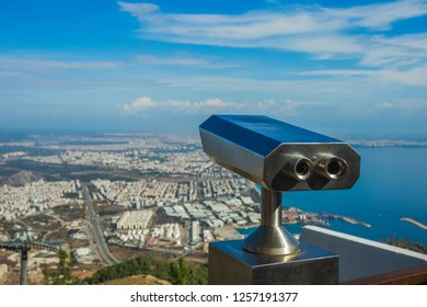 Closeup view of coin operated binocular viewer for looking in details at beautiful summer cityscape landscape. Antalya, Turkey. Happy summer holidays and sightseeing concept. Horizontal photography.