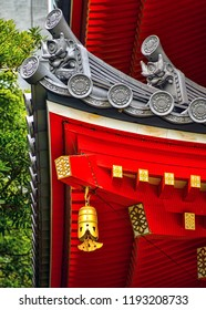 Closeup View of Corner Eave Gable Decorations on Historic Red Buddhist Temple. Dual Oni Ogre Faces and Gold Hanging Bell. Architectural Elements (Tochoji, Fukuoka, Japan)