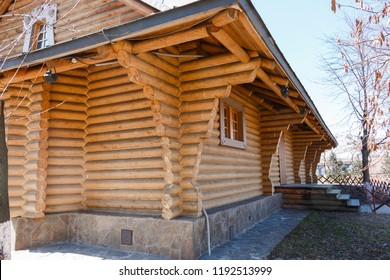 Close-up view of corner of wooden house made of natural logs with stone base. Wooden house made of logs. Ecological house.