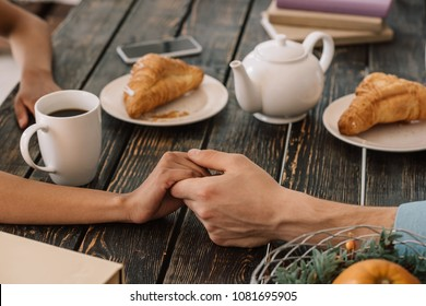 Close-up view of couple holding hands on table with breakfast