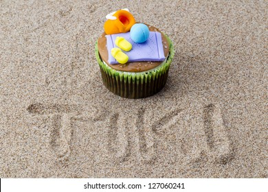 Close-up view of cupcake with decorative miniatures toppings on sand with tiki inscribed in the sand.