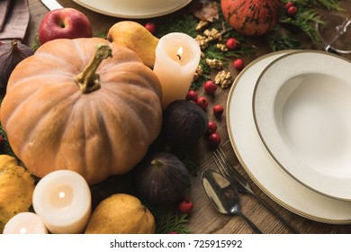 close-up view of cutlery, pumpkins, candles and fruits on table