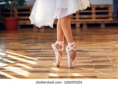 Close-up view of dancing legs of ballerina wearing white pointe ballet shoes in the dancing hall.