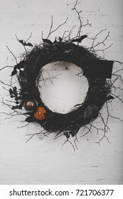 close-up view of decorative halloween wreath hanging on white brick wall