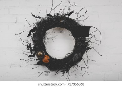 close-up view of decorative spooky halloween wreath hanging on white brick wall