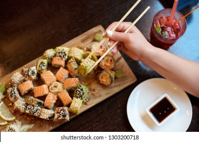 Close-up view of delicious rolling sushi served on the wooden board with chopsticks, soy sauce and cocktail