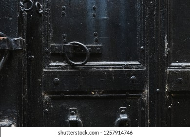 Closeup view of details of old black door. Horizontal color photography.