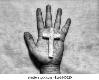 Closeup view of dirty grunge palm hand as sinner holding christian cross of Jesus, made from clay, dark concept with selective focus and monochrome process
