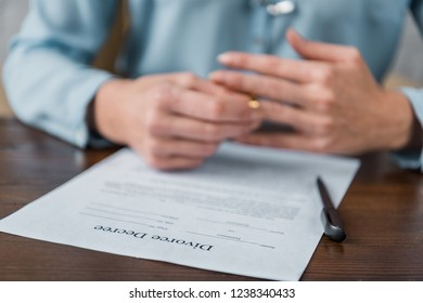 close-up view of divorce decree and woman taking off wedding ring behind