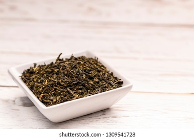 Close-up view of dry moroccan mint tea leaves with in small white ceramic plate on white table