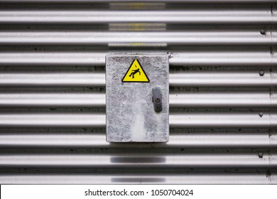 Closeup view of an electric box with a danger sign sticker representing an electrocuted person silhouette.
