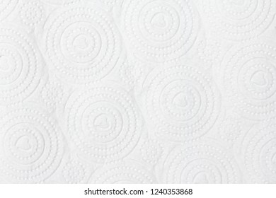 Closeup view of embossed surface texture of new white paper towel tissue from roll in heart-shape, dots, dashed and circular pattern. For wallpaper, backdrop and background with copy space