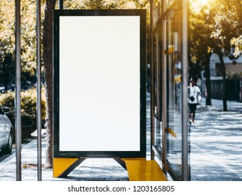 Close-up view of an empty billboard placeholder template inside of the city bus stop; blank advertising banner mock-up near the road; white empty informational signboard on the street