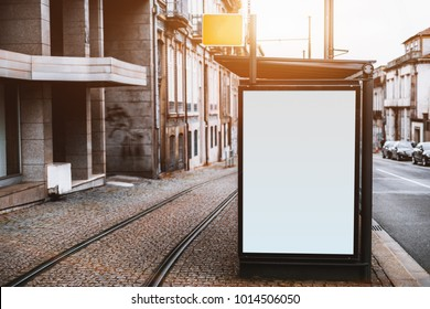 Close-up view of empty white informational banner mockup in urban settings between road and tramway; blank billboard placeholder template outdoors on city tram stop, pavement stone, sunny day