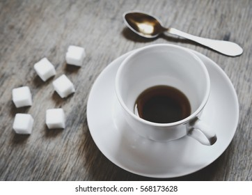 closeup view of a emty cup of coffee with sugar cubes. top view
