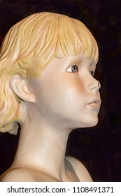 Closeup view of face of old retro mannequin girl with short blond hair and a chip in her nose and a spider behind her ear against dark background