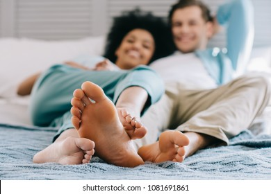 Close-up view of feet of multiracial couple staying in bed