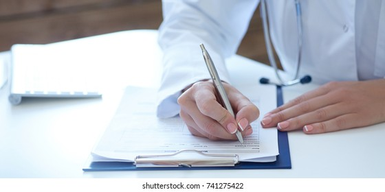 Close-up view of female doctor hands filling patient registration form. Health care and medical concept.