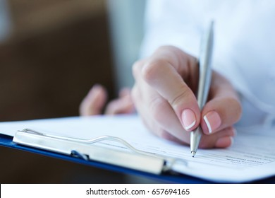 Close-up view of female doctor's hands filling patient registration or prescription form. Health care, medical and pharmacy concept.
