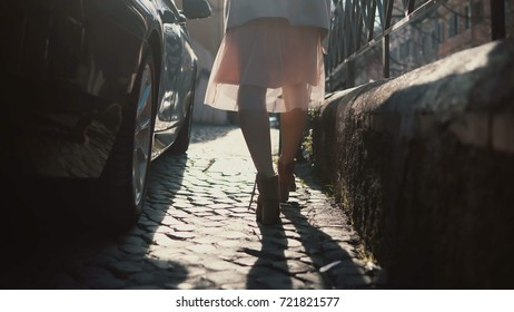 Close-up view of female feet walking through the urban street. Female in shoes and skirt going in the city centre.