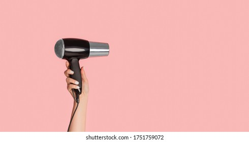 Closeup view of female hand showing modern hairdryer on pink background, empty space. Panorama