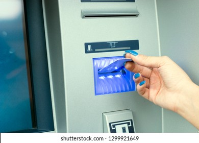 Close-up view of female hand using her credit card at the ATM