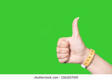 Closeup view of female hand wearing brown entrence wristband of hotel resort or entertainment park. Hand isolated on green chromakey background. Horizontal color photography.