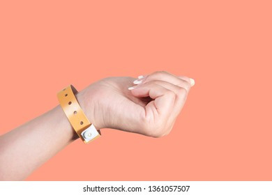 Closeup view of female hand wearing brown entrance wristband of hotel resort or entertainment park. Hand isolated on bright orange background. Horizontal color photography.
