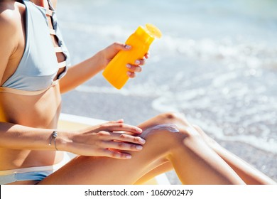 Close-up view of female hands applying tanning lotion for legs. Sunbathing. Summertime.