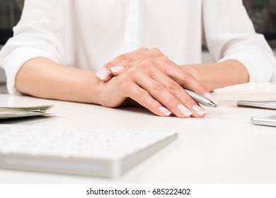 close-up view of female hands with beautiful manicure holding pen at workplace