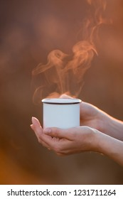 Closeup view of female hands gengtly holding mug with morning hot coffee and hot steam rasing