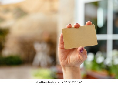 Close-up view of female hands holding a gold credit card, while using a laptop and typing on the keaboard. Online shopping concept. Woman with banking card