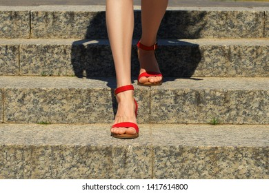 Closeup view of female legs in sandals descending the stairs in the city