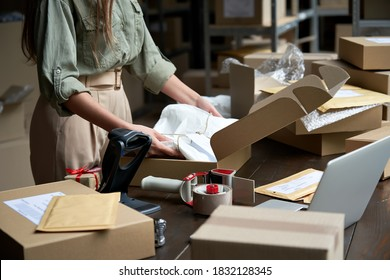 Closeup view of female online store small business owner seller entrepreneur packing package post shipping box preparing delivery parcel on table. Ecommerce dropshipping shipment service concept.