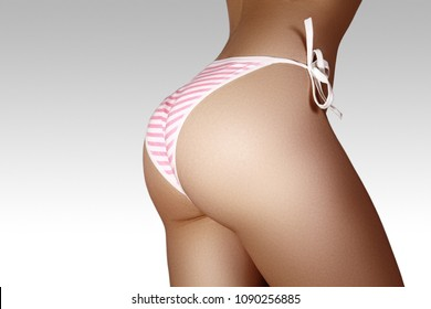 Close-up view of Female Sport Tanned Buttocks in Sexy Pink Panties. Perfect Body with Tan Hips and Fit Waist on light background